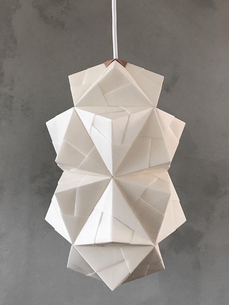 Foto af original håndfoldet Sonobe Light papirlampe lavet af Charlotte Brandt, model Cala str. small mod klakmalet grå væg