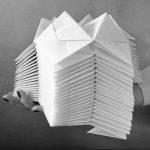En stak håndfoldede papirmoduler til produktion af SonobeSense papirlamper. Holdt elegant i hånden af designer Charlotte Brandt