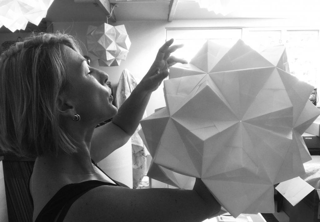 Foto af Charlotte Brandt i papirværkstedet hvor hun er ved at lave en stor håndfoldet og dråbeformet papirlampe model Amaea