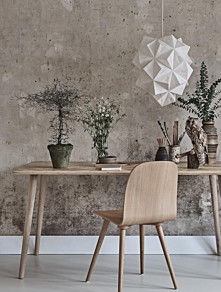 Dette er et foto af stor Amaea med lyset slukket så man kan se alle folderne i papiret den fine bløde hvide overflade. Lampen hænger over et skrivebord i et smukt miljø med gammel rustik og rå mur og lækre møbler i egetræ. På bordet er også skrivgrej og en udstoppet hornugle.
