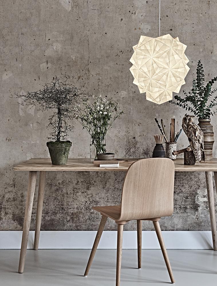 Dette er et foto af stor Amaea med lyset tændt så man kan se alle folderne i papiret og variansen i lyset. Lampen hænger over et skrivebord i et smukt miljø med gammel rustik og rå mur og lækre møbler i egetræ. På bordet er også skrivgrej og en udstoppet hornugle.
