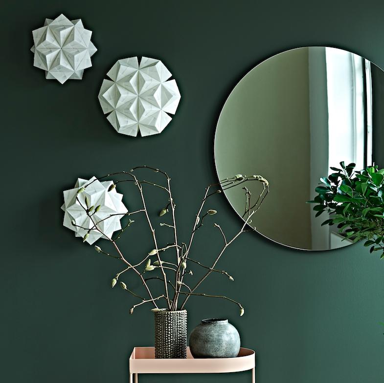 Foto af tre væglamper på en smuk mørkegrøn væg. Lamperne er model Cenora, 2 små og en stor, alle fint foldet i det hvide Sonobe Light papir - som fine lysende blomster eller skyer på væggen. Ved siden af lamperne er et rundt spejl og under et moderne bakkebord i sart rosa med et arrangement af vaser og magnoliegrene.