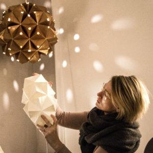 Charlotte Brandt i sit Sonobe Light papirværksted på Vesterbrogade. I baggrunden ses en stor unik foldet lampe i tykt kobberpapir som hun lavede til en udstilling for taastrup Kunstforening
