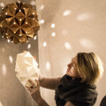 Charlotte Brandt folder en håndlavet papirlampe i Sonobe Light værkstedet, unik xl håndlabet kobberlampe i baggrundern