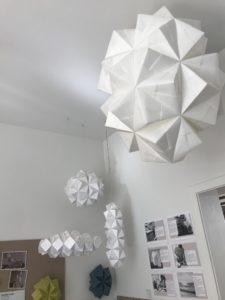 XL papirfold, stor håndlavet papirlampe og andre modeller hænger fra loftet i papirværkstedet, designet og foldet af Charlotte Brandt