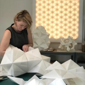 Charlotte folder XL-papir lamper i sit papirværksted