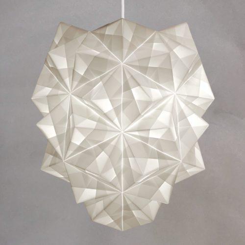 Sonobe Light, håndfoldet papirpendel model Amaea, med lyset tændt mod lys varm grå kalkmalet væg