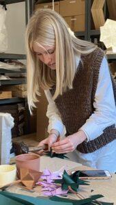 Erhvervspraktikant Signe folder julestjerner i papirværkstedet hos Sonobe Light
