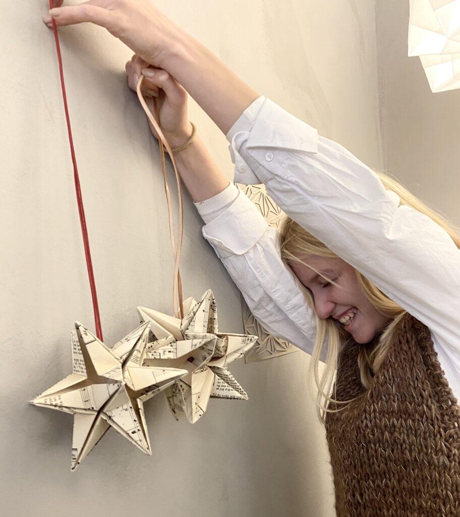 Erhvervspraktikant Signe med en foldet julestjerne hun har lavet