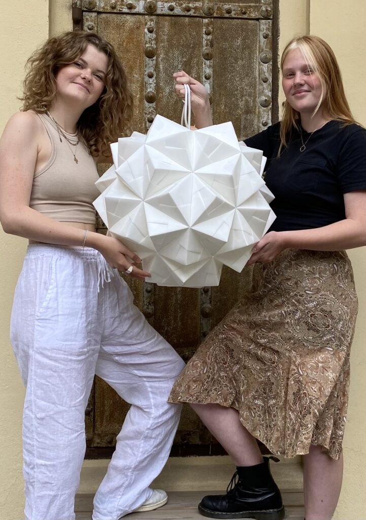 Coco og Minna på trappen i gården bag papir- og lampeværksteder med lampe